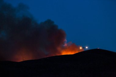 Firefighting plane soars from behind a hill after dropping flame retardant. Lights on each wing glow in the darkness