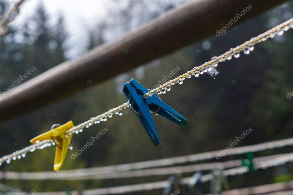 plastic clothesline with clothespin and dew drops on closeup.