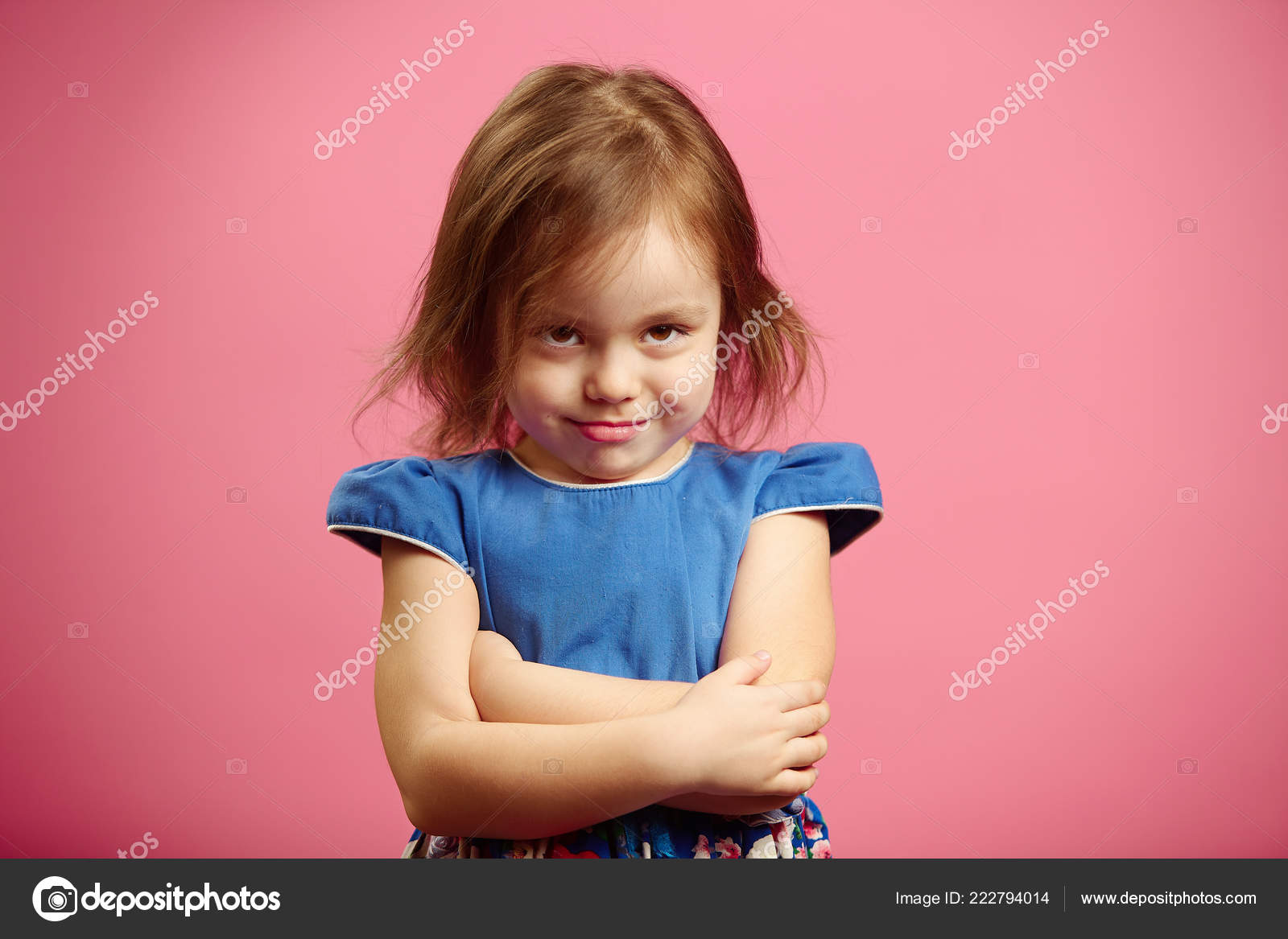 a80096b534ac Sad little girl with crossed on chest arms looks from under with deep brown  eyes and stands beside pink wall dressed in blue dress emotional portrait  photo.