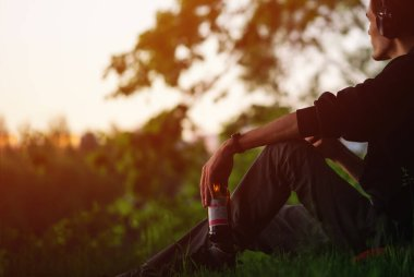 A man sits on the grass in the Park, listening to music, drinking beer. Relax and enjoy your life