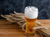 Mlhavé sklo lehkého piva na dřevěném stole a pšenici
