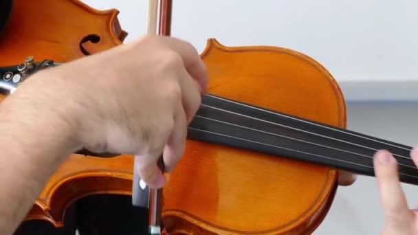 Egy zenész hegedül, egy közeli hegedűoktató.,