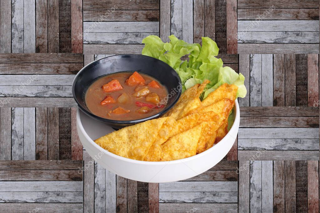 Ready served of crisy wonton with Japanese yellow curry topped green oak