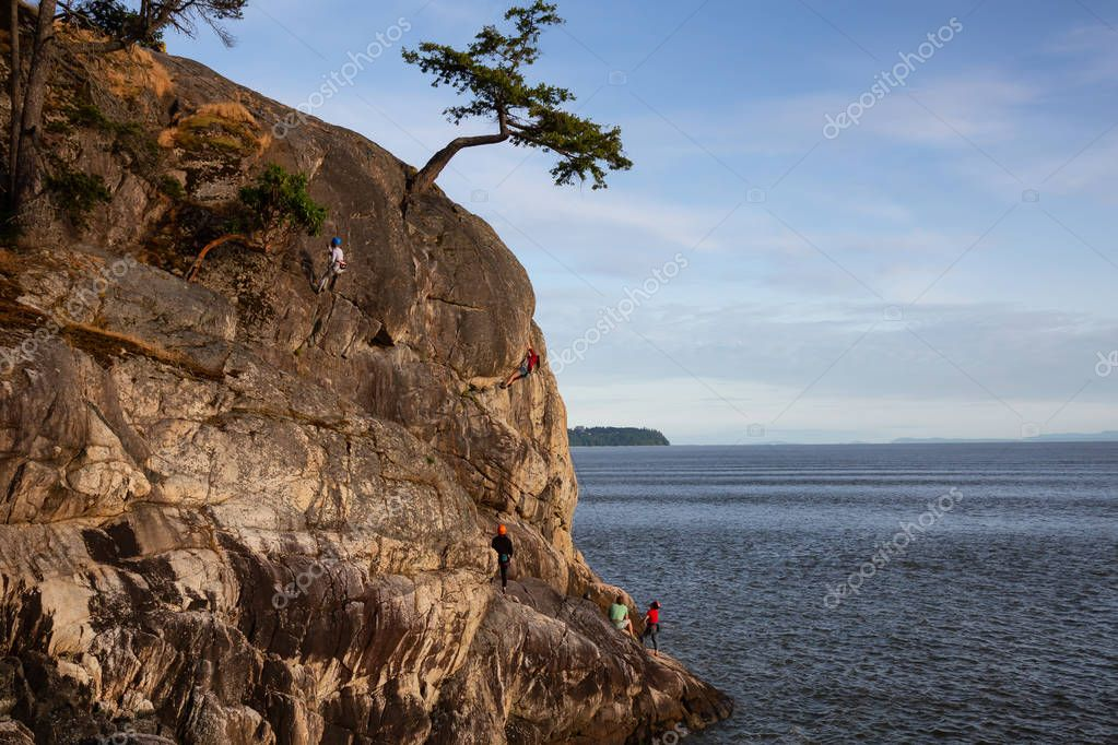 West Vancouver, British Columbia, Canada - May 30, 2018: People rock climbing outdoors on a rocky shore.