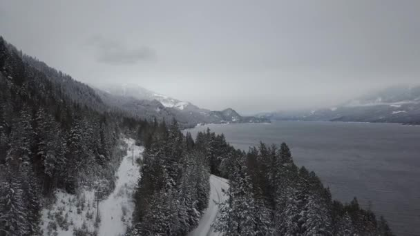 Letecký pohled na sněhu zahrnuty silnice kolem jezera Kootenay v zimním období. Ve vnitrozemí Britská Kolumbie, Kanada