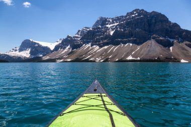 Kayaking in a glacier lake during a vibrant sunny summer day. Taken in Bow Lake, Banff National Park, Alberta, Canada.