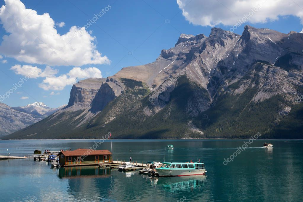 Banff, Alberta, Canada - June 20, 2018: Boats at the dock with a beautiful Canadian Mountain Landscape in the background.