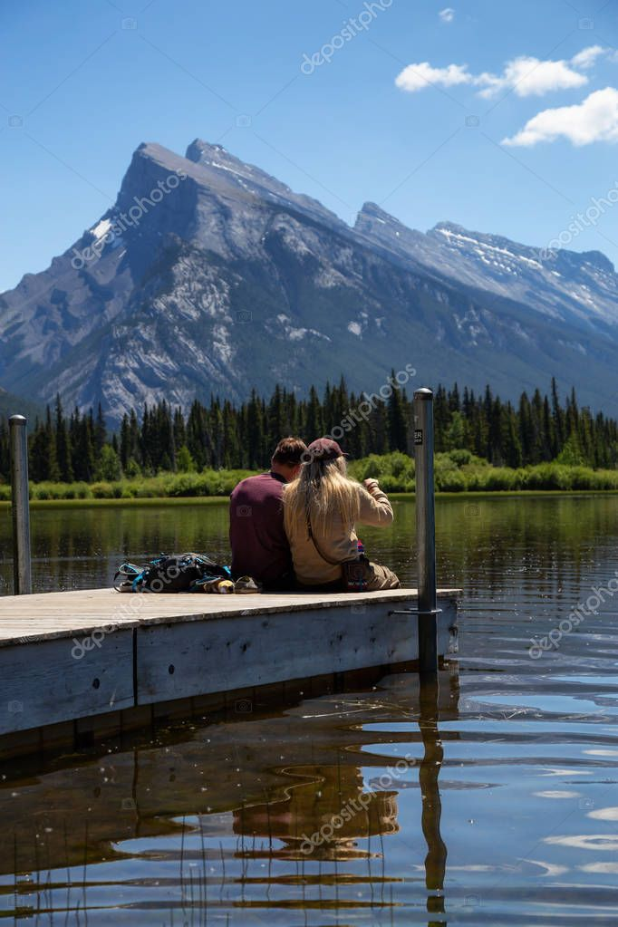 Banff, Alberta, Canada - June 19, 2018:  Couple friends are enjoying the beautiful view on a wooden dock.