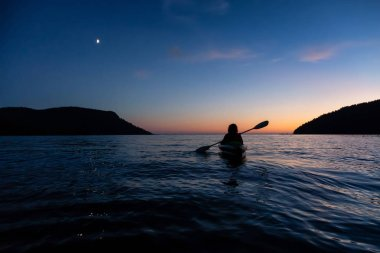 Sea Kayaking in the Pacific Ocean during twilight after summer sunset. Taken in San Josef Bay, Vancouver Island, BC, Canada.