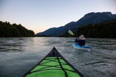 """Картина, постер, плакат, фотообои """"каякинг в реке, окруженной канадскими горами во время яркого летнего заката. снято в сквамише, британская колумбия, канада ."""", артикул 213334264"""