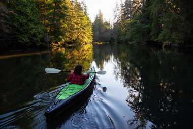 Girl kayaking in the beautiful river during a sunny summer morning. Taken in San Josef Bay, Cape Scott, Northern Vancouver Island, BC, Canada.