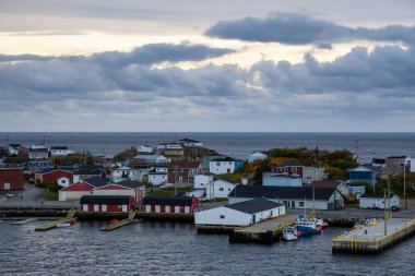 Homes in a little town on the rocky Atlantic Ocean Coast during a cloudy sunset. Taken in Channel-Port aux Basques, Newfoundland, Canada.
