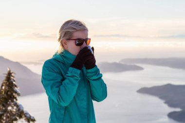 Young Caucasian Girl drinking warm beverage on top of a mountain during a beautiful winter sunset. Taken on Mnt Harvey, near Vancouver, BC, Canada.