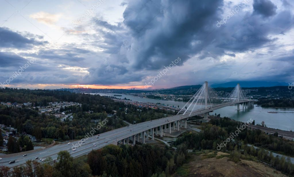 Aerial panoramic view of Trans Canada Highway near the Port Mann Bridge during a dramatic cloudy sunset. Taken in Surrey, Vancouver, BC, Canada.