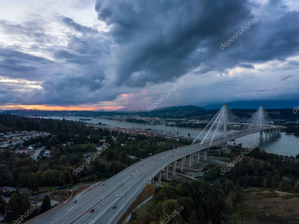 Aerial view of Trans Canada Highway near the Port Mann Bridge during a dramatic cloudy sunset. Taken in Surrey, Vancouver, BC, Canada.