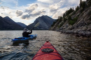 Adventurous Man Kayaking in Glacier Lake surrounded by the beautiful Canadian Rocky Mountains during a cloudy summer sunset. Taken in Upper Waterton Lake, Alberta, Canada.