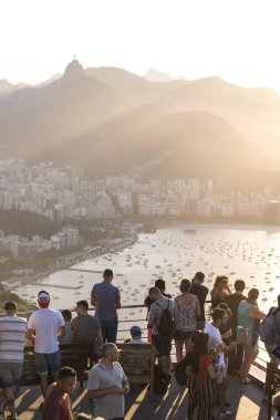 Tourists watching the sunset from the Sugar Loaf Mountain with beautiful landscape of the city and mountains, Rio de Janeiro, Brazil