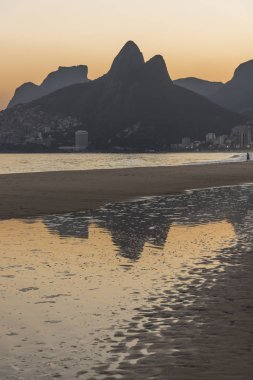 Beautiful landscape of beach, mountains and the ocean with water reflections during sunset time, seen from Ipanema Beach in the city of Rio de Janeiro, Brazil
