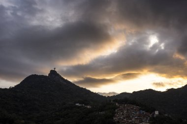Beautiful view to Corcovado Mountain and Christ the Redeemer Statue during sunset time with heavy greay and orange clouds in the landscape, Rio de Janeiro, Brazil