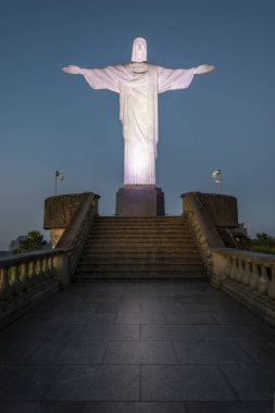 Beautiful landscape with a view to Christ the Redeemer Statue (Cristo Redentor) on top of Corcovado Mountain (Morro do Corcovado) with early morning light at dawn and blue sky in Rio de Janeiro, Brazil