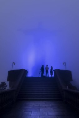Group of photographers under Christ the Redeemer statue (Cristo Redentor) on top of Corcovado Mountain (Morro do Corcovado) with blue lights and cloudy weather, Rio de Janeiro, Brazil