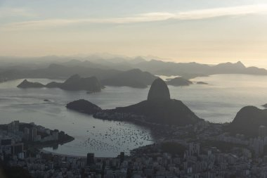 Beautiful landscape with a view to the Sugar Loaf bay area, the city and mountains seen from Christ the Redeemer Statue (Cristo Redentor) on top of Corcovado Mountain (Morro do Corcovado) during the sunrise in Rio de Janeiro, Brazil
