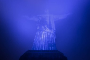 Christ the Redeemer statue (Cristo Redentor) on top of Corcovado Mountain (Morro do Corcovado) with blue lights and cloudy weather, Rio de Janeiro, Brazil