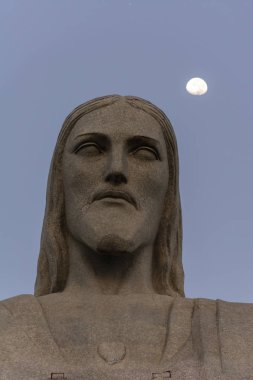 Christ Statue with the moon during sunrise in Corcovado Mountain