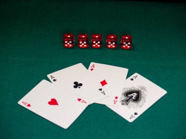 The four aces of a poker deck and several dice on a green mat