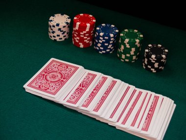 A deck of poker cards and poker chips of various colors on a green mat