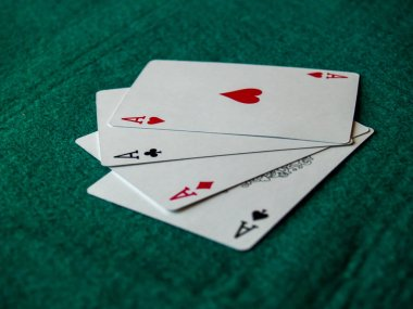 The four aces of a poker deck on a green mat