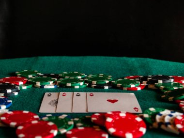 The four aces of a poker deck and poker chips of various colors on a green mat