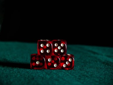 Several red dice with white dots on a green mat