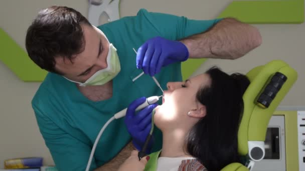 junge Frau sitzt auf Zahnarztstuhl, während ihr männlicher Zahnarzt ihre Zähne repariert.