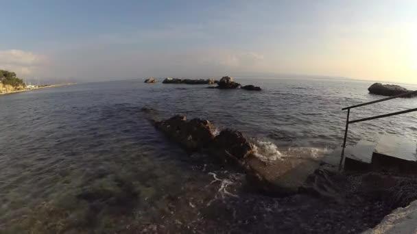 žebřík vedoucí do moře při západu slunce