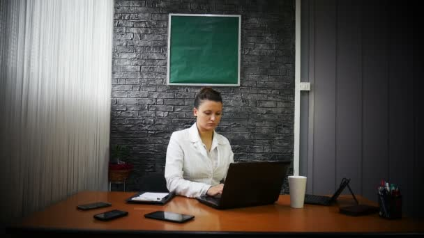 Obchodní žena v bílém obleku před laptopem pije kávu