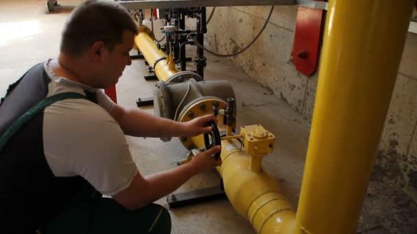 Muž otevře ventil dodávky plynu do kotle