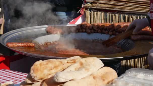 A séf kiveszi a sült kolbászt az olajból. Utcai élelmiszer-értékesítés.