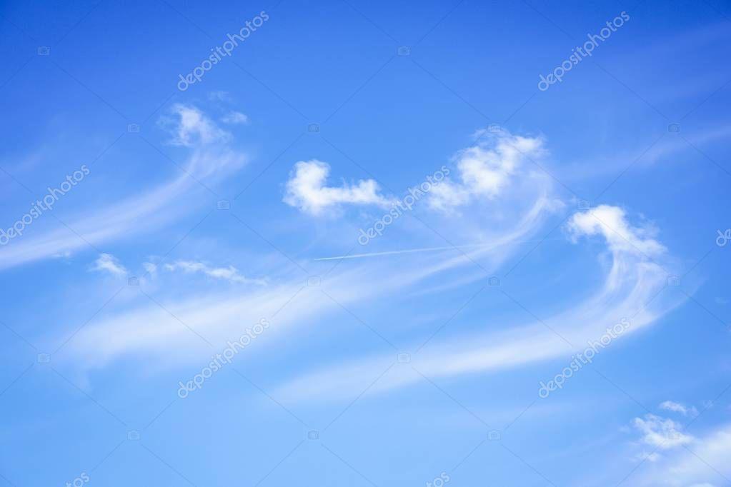White clouds on a blue sky background. Clouds like a sea waves