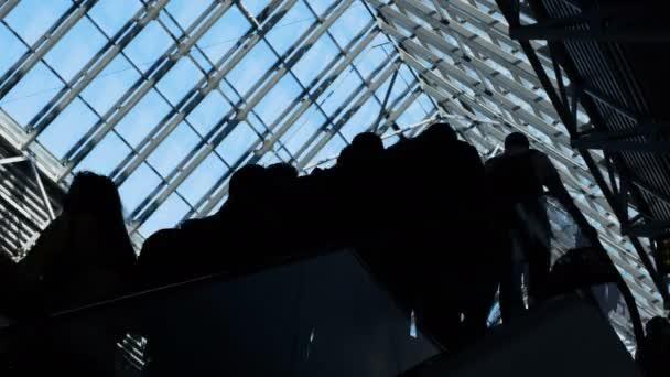 Gruppe von Menschen Silhouetten bewegen sich auf Rolltreppe