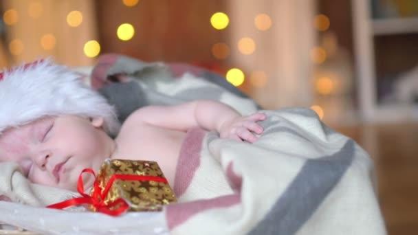 Weihnachten schläft ein neugeborenes Baby mit Weihnachtsmann-Mütze in einem Korb liegend und hält ein kleines Geschenk in der Hand, auf einem hellen festlichen Hintergrund