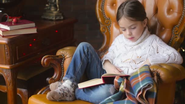 Mädchen sitzt auf einem Stuhl und liest interessiert Märchen