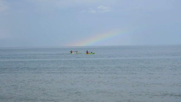 Skupina mladých lidí plave na kajaky v moři proti krásné duhové