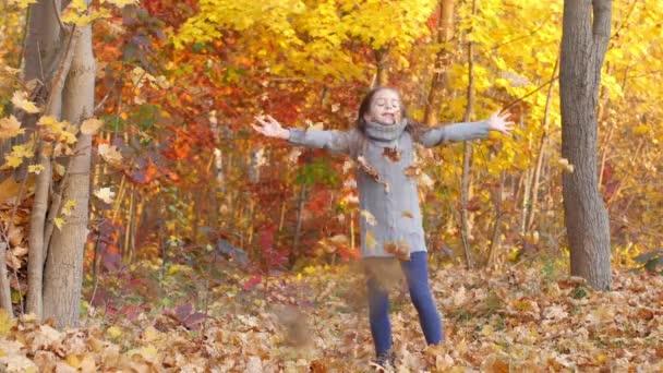 Šťastná dívka hraje a baví se v podzimním parku, hází listí a směje se
