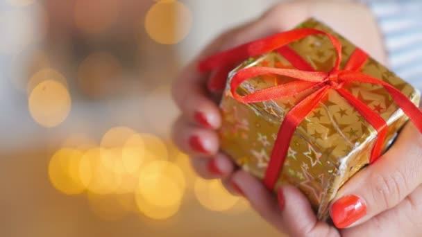 svátky, detail dívčí ruky opatrně uchopte malou krabičku s dárkem v zlaté papíru s červenou stužkou, na jasném pozadí, slavnostní