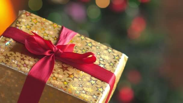 svátky, detail dívka rozváže červenou stuhou s dárkem, na jasném pozadí, slavnostní