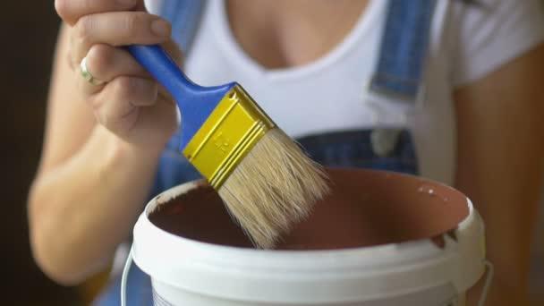 Nahaufnahme, professionelles Malermädchen befeuchtet Pinsel mit Farbe, bereitet sich auf das Malen vor