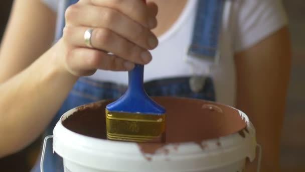 Nahaufnahme, ein Mädchen professionelle Malerin mokay und zeigt Pinsel mit brauner Farbe