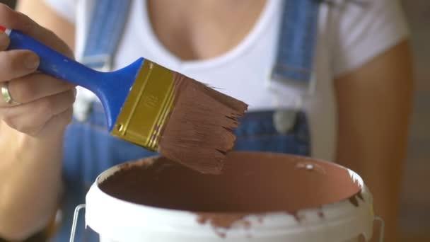 Mädchen professionelle Malerin spöttisch Pinsel in brauner Farbe
