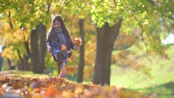 Happy Girl in Coat Walks in a Sunny Autumn Park. Dítě drží padlé žluté listy v rukou. Děti Odpočiňte si na čerstvém vzduchu. koncept dětství.
